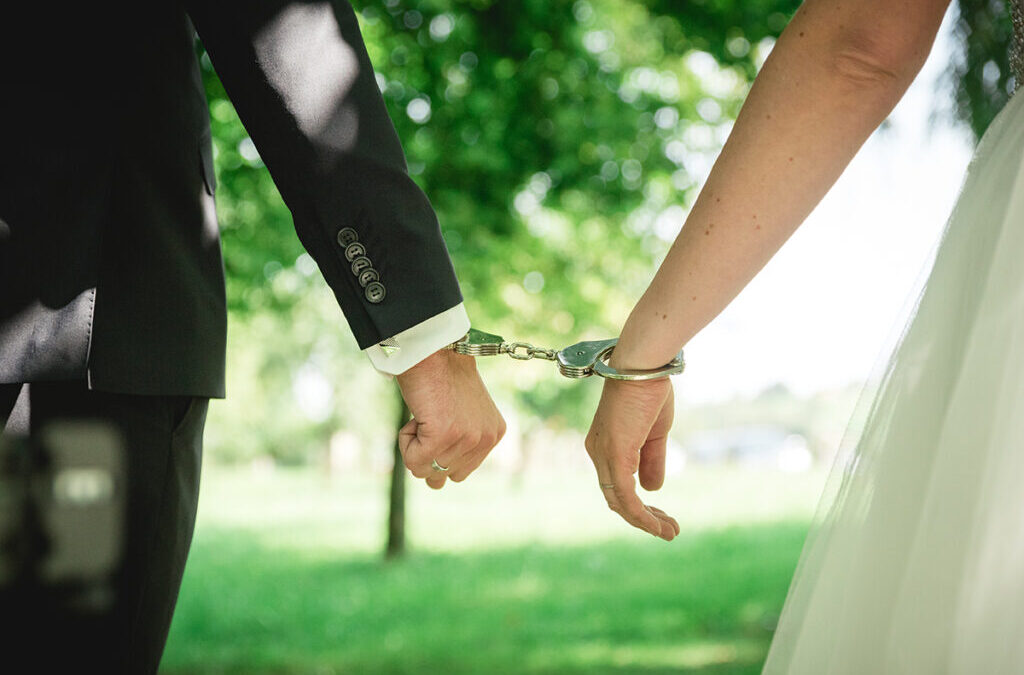Bride and groom walking outdoors with handcuffs